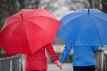 lluvia paraguas: Una vista de cerca de una pareja caminando de la mano a través de la lluvia con paraguas y ropa de lluvia. Foto de archivo