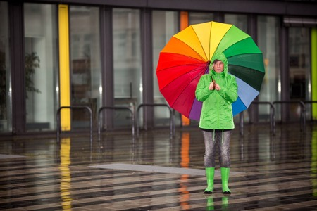 A woman is waiting in the rain with her rain cloth.