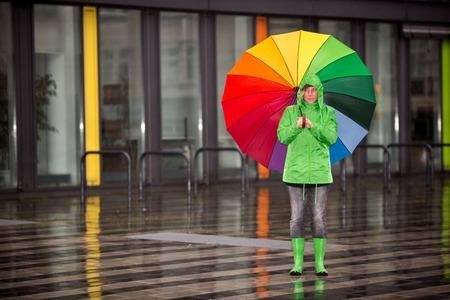 botas de lluvia: Una mujer está esperando bajo la lluvia con su tela de lluvia.
