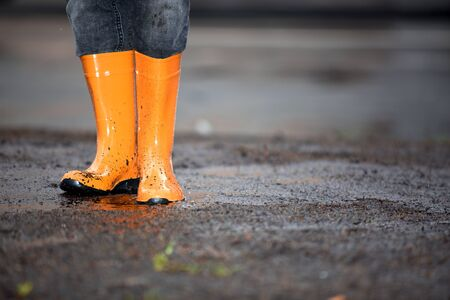 smut: A pair of orange rubber boots in a dirty puddle. Stock Photo