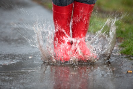 rain coat: Feets with rubber boots are jumping into a big puddle with splash.