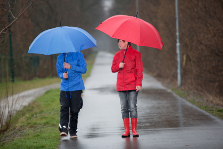 brolly: A raincoat dressed couple with umbrella talking in the rain. Stock Photo