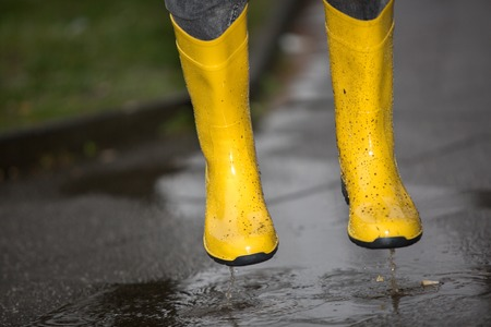 smut: A pair of yellow boots are jumping into a puddle. Stock Photo