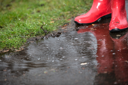 smut: A pair of red boots in a puddle with water drops in rain. Stock Photo