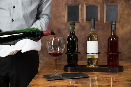 alcohol server: A waiter is pouring red wine into a glass. Vine bottles with a chalkboard in the background.