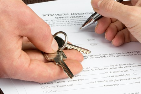 A woman is filling out a room rental agreement document with a key and pen in her hand.
