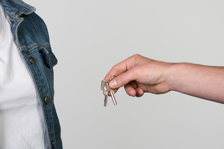 landlord: A landlord hands over a Apartment key to a woman, isolated on grey. Stock Photo