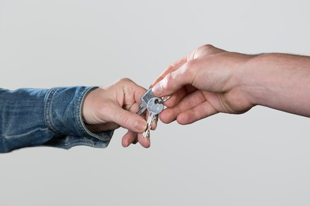 key handover: A Key handover from a landlord to a tenant, isolated on a grey background.