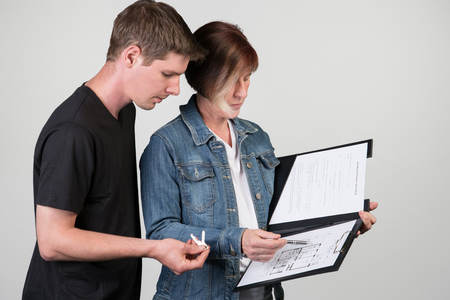 accommodation broker: A landlord explains the floor plan to the tenant. Isolated on a grey background. Stock Photo