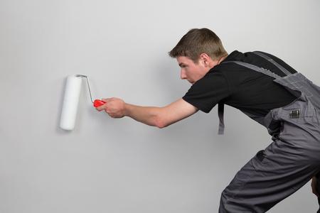 pintor de casas: Un pintor se agach� en traje de trabajo aislado en un fondo gris.