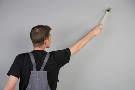 redecorate: A young Painter is using a brush over his head to paint the grey wall. Stock Photo