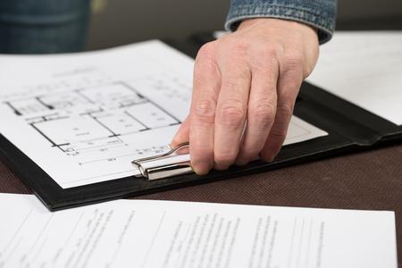 Einige Grundrisse sind von einer Architektin in ein Klemmbrett geheftet. Standard-Bild - 49218625
