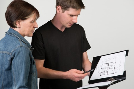 floorplan: A young landlord is explaining the floorplan to a female client isolated on a grey background. Stock Photo