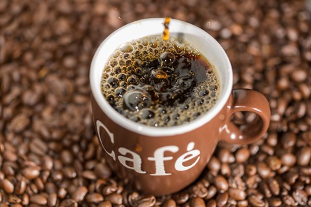 strew: Some drops of coffee are falling into a cup, decorated with some coffee beans.