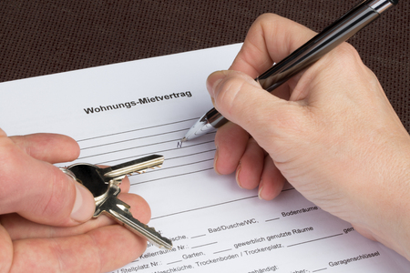 A woman is filling out a german tenancy agreement with keys in her hand.