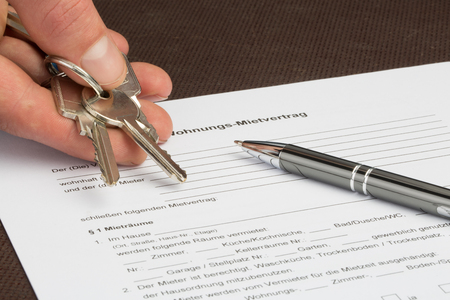 A german rental agreement with house keys in one hand. A pen is lying on the document.