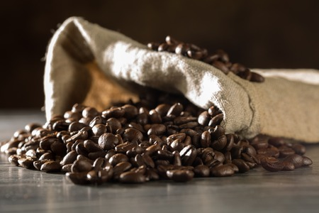 Some roasted coffee beans within a burlap bag