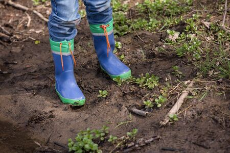 smut: A youngster is standing in a mud with his rainboots.