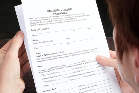 filled out: A woman is reading a room rental form. The agreement is not filled out so far.