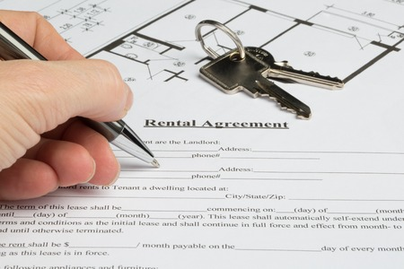 agency agreement: A people starts to fill out a a rental agreement. The floor plan and the keys from the apartment are in the background.