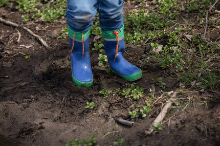 smut: A pair of kid boots in a muddy wet ground