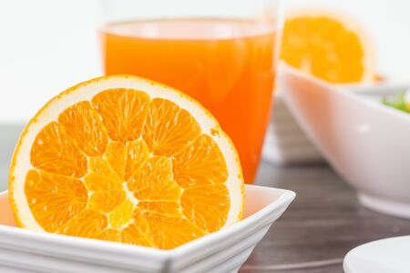 cutted: A half cutted orange fruit in a bowl infront of a glass of orange juice decorated with some other breakfast elements.