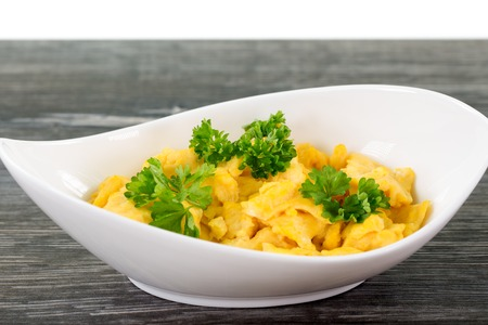 dish disk: A portion of scrambled eggs in a white bowl standing on a wooden table.