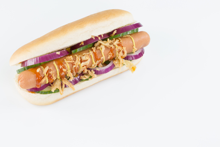 A fresh hotdog with sausage, onions, cocumbers, ketchup and mustard isolated on white.