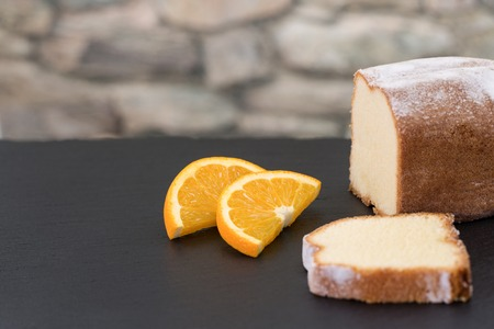 pices: A lemon cake on a roof slate decorated with two pices of orange fruit. A stone wall in the background.