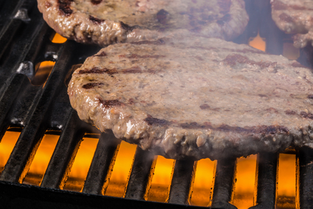 grate: Some patties of ground meat on a cooking grate with flames and smoke under the cooking grate. Stock Photo