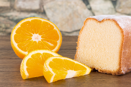A powdered lemon cake with fresh sliced orange fruits on a wooden table. A blurred stone wall in the background.