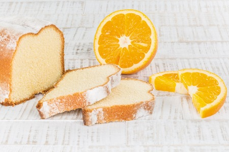 A sliced lemon cake with some fresh orange fruits on a wooden table.