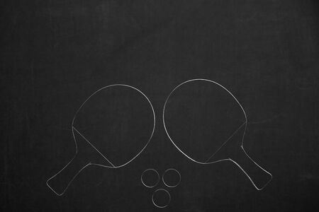 Two table tennis rackets with three balls drawed with chalk on a dark chalkboard.