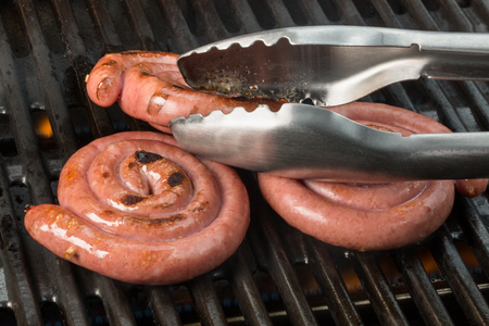 grill tongs sausage: Some circled sausages on a grill. One sausage is going for a turn by a tongs.