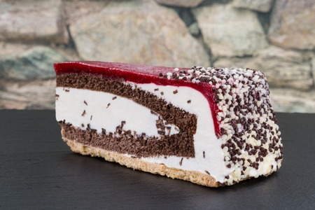 torte: A piece of cherry cream torte on a dark slate with a stone wall in the background.
