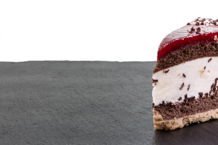 torte: A piece of cherry cream torte on a slate  isolated on white with copyspace. Stock Photo