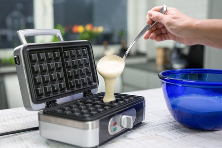 A woman is pouring dough on a waffle iron in their kitchen. Stock Photo