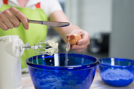 smashing: A housewife is smashing an egg into a bowl of dough in her modern kitchen.