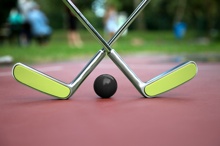 double game: A minigolf scenery consist of two crossed minigolf rackets and a black ball on a clean ground with copyspace. Stock Photo