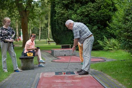 Eine gemeinsame Familie bei Minigolf-Spiel. Der männliche Senior an der Flocke ausrichtet den Schläger den Ball zu schlagen.