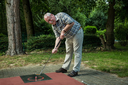 A pensioner at a minigolf court has a lot of fun during his shot.
