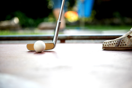 A closeup view from a professional minigolf player hitting a white ball with an iron racket.