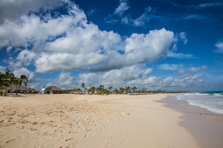 A wide caribbean beach at a cloudy day with ocean.