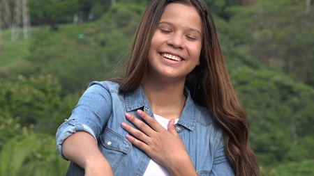 Teen Girl With Hand Over Heart Stock Photo