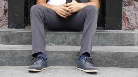 Legs And Feet Of Man Sitting