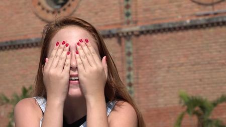 La muchacha adolescente que cubre sus ojos