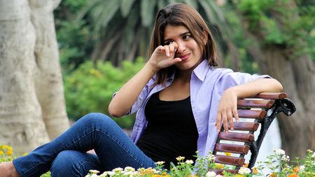 tearful: Tearful Youthful Female Sitting On Bench