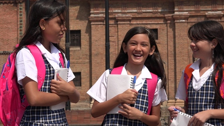 Young Colombian Girl Students Holding Notebooks Wearing School Uniforms Archivio Fotografico