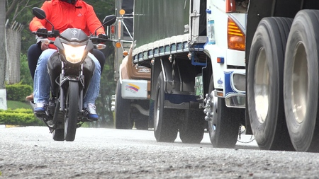Motorcycle Riding With Trucks Editorial
