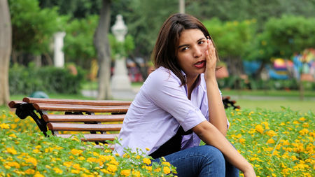 Anxious Latina Girl Sitting In Park Stock Photo